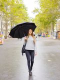 A girl with a black umbrella is hiding from the rain. A young, beautiful girl with a black umbrella hiding from the rain Stock Photos