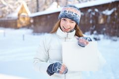 Young beautiful girl with blank banner. Winter. Royalty Free Stock Images