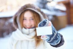 Young beautiful girl with blank visiting card. Winter. Royalty Free Stock Image