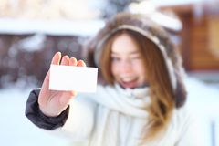 Young beautiful girl with blank visiting card. Winter. Royalty Free Stock Photography