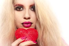 Young beautiful girl with blond hair holding a heart symbol Stock Photography
