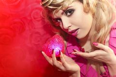 Red heart. Young beautiful girl with blond hair holding a heart symbol red color Royalty Free Stock Photography