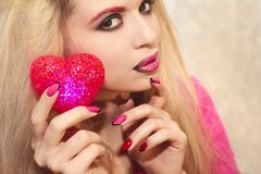 Red heart. Young beautiful girl with blond hair holding a heart symbol red color Stock Image