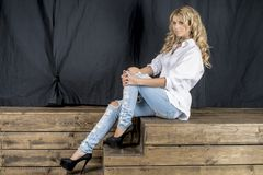 Young beautiful girl blonde in a white shirt and jeans with gaps stock image