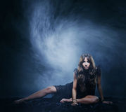 Young, beautiful girl in blowing silk over dark background Royalty Free Stock Images