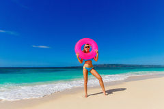 Young beautiful girl in blue bikini having fun on a tropical bea. Ch with rubber ring for swimming. Blue sea and sky in the background. Summer vacation concept Stock Images