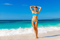 Young beautiful girl in blue bikini having fun on a tropical bea. Ch. Blue sea and sky in the background. Summer vacation concept Stock Photos