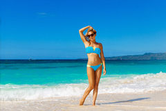 Young beautiful girl in blue bikini having fun on a tropical bea. Ch. Blue sea and sky in the background. Summer vacation concept Royalty Free Stock Image