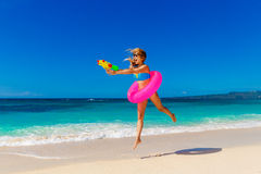 Young beautiful girl in blue bikini having fun on a tropical bea. Ch with toy water guns and rubber ring for swimming. Blue sea and sky in the background. Summer Stock Photos