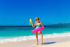 Young beautiful girl in blue bikini having fun on a tropical bea. Ch with toy water guns. Blue sea and sky in the background. Summer vacation concept Stock Image