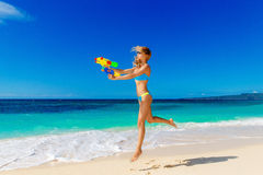 Young beautiful girl in blue bikini having fun on a tropical bea. Ch with toy water guns. Blue sea and sky in the background. Summer vacation concept Royalty Free Stock Photography