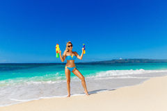 Young beautiful girl in blue bikini having fun on a tropical bea. Ch with toy water guns. Blue sea and sky in the background. Summer vacation concept Royalty Free Stock Images