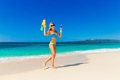 Young beautiful girl in blue bikini having fun on a tropical bea. Ch with toy water guns. Blue sea and sky in the background. Summer vacation concept Stock Images