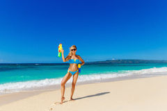 Young beautiful girl in blue bikini having fun on a tropical bea. Ch with toy water guns. Blue sea and sky in the background. Summer vacation concept Stock Photo