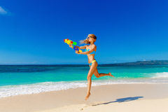 Young beautiful girl in blue bikini having fun on a tropical bea. Ch with toy water guns. Blue sea and sky in the background. Summer vacation concept Royalty Free Stock Photos