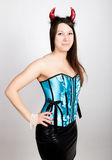 Young beautiful girl in blue corset with red horns looks like pretty Devil Royalty Free Stock Photography