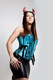 Young beautiful girl in blue corset with red horns looks like pretty Devil Royalty Free Stock Photo