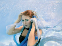 Young beautiful girl in blue dress underwater Royalty Free Stock Photo