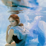 Young beautiful girl in blue dress underwater Royalty Free Stock Photos