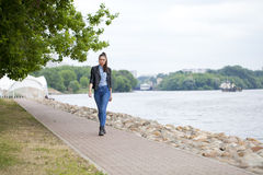 Young beautiful girl in blue jeans and a blue shirt on the backg Royalty Free Stock Photography