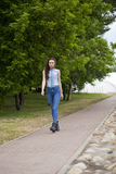 Young beautiful girl in blue jeans and a blue shirt on the backg Royalty Free Stock Image