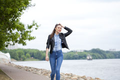 Young beautiful girl in blue jeans and a blue shirt on the backg Stock Photo