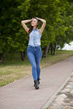 Young beautiful girl in blue jeans and a blue shirt on the backg Royalty Free Stock Photos