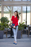Young beautiful girl in blue jeans and red shirt on the backgrou Royalty Free Stock Image