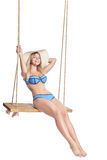 Young beautiful girl with blue swimsuit riding on swing stock image