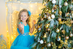 Young beautiful girl in blue white elegant evening dress sitting on floor near christmas tree and presents on a new year Stock Photos
