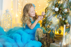 Young beautiful girl in blue white elegant evening dress sitting on floor near christmas tree and presents on a new year Royalty Free Stock Images