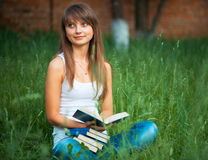 Young Beautiful girl with book in the park on green grass Royalty Free Stock Image