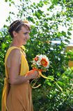 Young beautiful girl bride in a bright orange dress. Summer bouquet in hands of the . Decoration  flowers in their hair Stock Photography