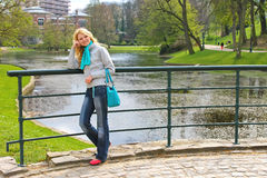 Young beautiful girl on a bridge in a park Stock Photo