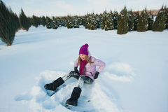 The young beautiful girl in bright clothes is sitting in the snow, laughing, winter holidays Royalty Free Stock Photo