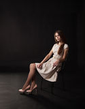 Young beautiful girl in a bright dress sitting on the chair Stock Photography