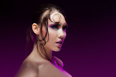 Young beautiful girl bright makeup with a wet look shine, dark background Stock Photo