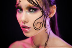Young beautiful girl bright makeup with a wet look shine, dark background Royalty Free Stock Photo