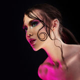Young beautiful girl bright makeup with a wet look shine, dark background Stock Images