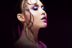 Young beautiful girl bright makeup with a wet look shine, dark background Royalty Free Stock Image