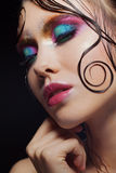 Young beautiful girl bright makeup with a wet look shine, dark background Royalty Free Stock Images