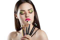 Young beautiful girl with bright makeup. A woman holds a professional makeup brushes Royalty Free Stock Image