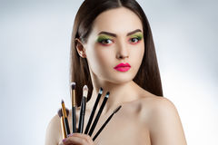 Young beautiful girl with bright makeup. A woman holds a professional makeup brushes Stock Photos