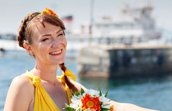 Young beautiful girl in the bright orange bride on a background of lake. Summer bouquet in hands  the . Royalty Free Stock Photo