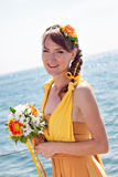 Young beautiful girl in the bright orange bride on a background of lake. Summer bouquet in hands  the . Stock Photo