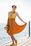 Young beautiful girl in the bright orange bride on a background of lake. Summer bouquet in hands  the . Stock Photos