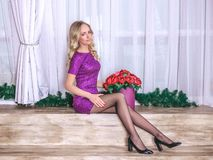 Young beautiful girl in a brilliant purple dress sitting with box of multicolored roses.  royalty free stock image