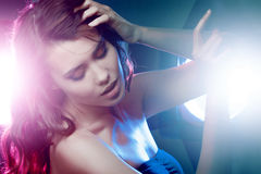 Young beautiful girl brunette, amid spotlight. Night club, dance culture. Effect of illumination Royalty Free Stock Images