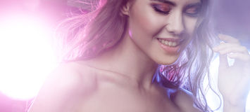 Young beautiful girl brunette, amid spotlight. Night club, dance culture. Effect of illumination Stock Image