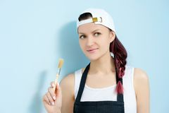 Girl painter, designer and worker paints a roller and brush the wall. Royalty Free Stock Photo